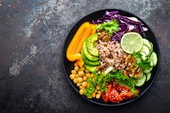 Buddha bowl dish with brown rice, avocado, pepper, tomato, cucumber, red cabbage, chickpea, fresh lettuce salad and walnuts. Healt royalty free stock photography