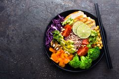 Buddha bowl dish with chicken fillet, brown rice, avocado, pepper, tomato, broccoli, red cabbage, chickpea, fresh lettuce salad, p. Ine nuts and walnuts. Healthy Stock Image