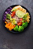 Buddha bowl dish with chicken fillet, brown rice, avocado, pepper, tomato, broccoli, red cabbage, chickpea, fresh lettuce salad, p. Ine nuts and walnuts. Healthy Royalty Free Stock Images