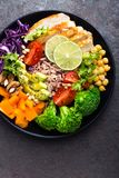 Buddha bowl dish with chicken fillet, brown rice, avocado, pepper, tomato, broccoli, red cabbage, chickpea, fresh lettuce salad, p. Ine nuts and walnuts. Healthy Royalty Free Stock Photos