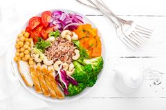 Buddha bowl dish with chicken fillet, brown rice, pepper, tomato, broccoli, onion, chickpea, fresh lettuce salad, cashew and walnu. Ts. Healthy balanced eating Royalty Free Stock Photos