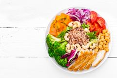 Buddha bowl dish with chicken fillet, brown rice, pepper, tomato, broccoli, onion, chickpea, fresh lettuce salad, cashew and walnu. Ts. Healthy balanced eating stock photo