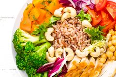 Buddha bowl dish with chicken fillet, brown rice, pepper, tomato, broccoli, onion, chickpea, fresh lettuce salad, cashew and walnu. Ts. Healthy balanced eating Stock Images