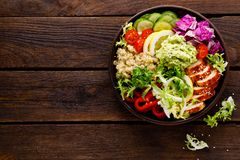 Buddha bowl dish. Healthy balanced lunch with quinoa, grilled chicken meat, lettuce salad, pepper, cucumber, tomato and avocado gu. Acamole with lemon. Top view stock image