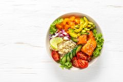 Buddha bowl with grilled salmon fish, fresh cucumber, tomato, onion, sweet pepper, avocado, lettuce salad and rice