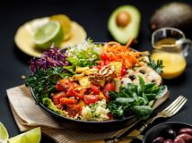 Buddha bowl of mixed vegetables, tofu cheese and groat on a black background. Gourmet and nutritious vegan meal. Healthy eating concept stock photo