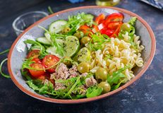 Buddha bowl. Pasta salad with tuna, tomatoes, olives, cucumber, sweet pepper. And arugula on rustic background stock photo