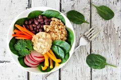 Buddha bowl with quinoa, hummus, mixed vegetables, over white wood. Healthy lunch bowl with quinoa, hummus and mixed vegetables, overhead scene on white wood Stock Photo