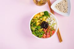 Buddha bowl with rice, mango, avocado and salmon.