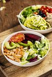 Buddha bowl salads on a wooden table. Closeup of two different buddha bowl salads, made with lettuce, cornsalad, quinoa, zucchini spaghetti, blueberries, beet royalty free stock images