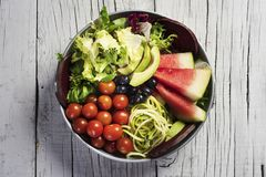 Buddha bowl on a white wooden table. High angle view of an appetizing buddha bowl, made with avocado, cornsalad, lettuce, zucchini, blueberries, watermelon, beet stock photo