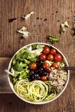 Buddha bowl on a wooden table. High angle view of an appetizing buddha bowl, made with lettuce, cornsalad, quinoa, zucchini spaghetti, blueberries and cherry royalty free stock photo