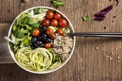 Buddha bowl on a wooden table. High angle view of an appetizing buddha bowl, made with lettuce, cornsalad, quinoa, zucchini spaghetti, blueberries and cherry stock photography