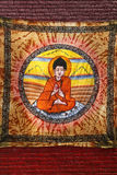 Buddha on brick wall. Picture of a colourful piece of fabric showing a representation of a Buddha. The fabric is attached outdoors on a red brick wall Stock Images