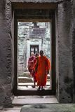 Buddhist monks passing through a stone temple hallway royalty free stock images