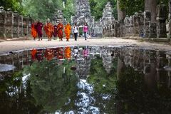 Buddhist monks reflection on water stock photography