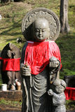 Buddha with Child. A statue of Buddha with a small child. The statue has a red clothe around it, this is very common in Japan royalty free stock photo