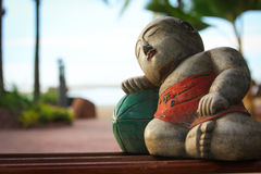 Buddha Chilling on a Melon. A sleeping Buddha-like figurine leaning on a melon near the water at the Anantara hotel in Bangkok, Thailand Royalty Free Stock Photos