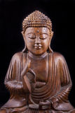 Buddha de madeira no fundo preto Fotografia de Stock Royalty Free