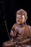 Buddha de madera en fondo negro Imagen de archivo libre de regalías