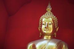 Buddha de oro contra un fondo rojo Imagenes de archivo