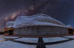 Buddha de reclinação branco sob a noite estrelado com w claramente leitoso imagens de stock royalty free