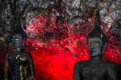 Buddha, in den alten Höhlen, rotes Licht glänzt durch die Rückseite Stockfotografie