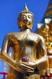 Buddha, der eine Blume hält Stockbild