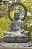 Buddha, der im japanischen Garten sitzt Lizenzfreies Stockfoto