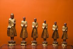 Buddha and disciples. Wooden statues of Buddha with five disciples against orange wall Stock Images