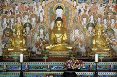 Buddhist temple : Buddha statue altar with disciples and decorative painting Royalty Free Stock Photos
