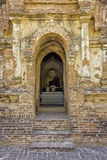 Buddha in doorway. View of entrance to brick temple with statue of sitting Buddha visible through doorway stock photo