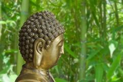 Buddha dorato è su un fondo dei boschetti di bambù Immagine Stock Libera da Diritti