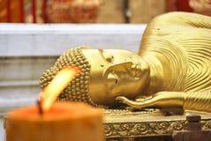 Buddha dorato addormentato dietro una candela bruciante Immagini Stock