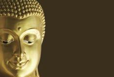 Buddha dorato affronta sul fondo di Brown fotografia stock