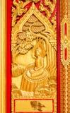 Buddha dorato che scolpisce sulla porta del tempio Fotografie Stock