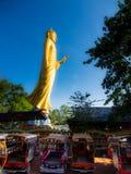 Buddha dorato grande in mezzo al mercato, cielo blu soleggiato Fotografie Stock