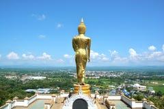 Buddha dorato sulla montagna con cielo blu a Wat Phra That Kao Noi immagine stock libera da diritti