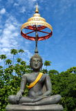 Buddha draped in orange cloth soaring into blue sky Royalty Free Stock Images