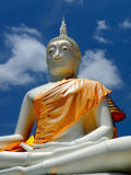 Buddha draped in orange fabric soars into blue sky Stock Images