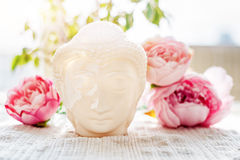 Buddha face. Buddha statue made of white marble with flowers. Concept of peace, calm and tranquility. Buddhist artifact Stock Image
