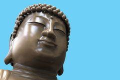 Buddha face. Close up of giant Buddha face on blue background Stock Image