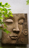 Buddha face sculpture on white wall Royalty Free Stock Photo