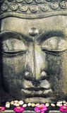 Buddha face statue with lotus flowers Royalty Free Stock Images