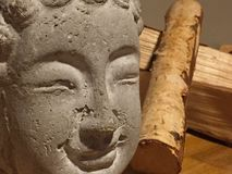Buddha face. Of stone and Wooden logs Stock Photos