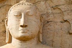 Buddha face on yellow stone Stock Photos