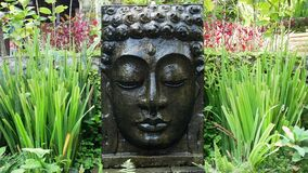 Buddha with falling water in the tropical garden in Ubud, Bali.