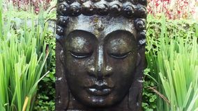 Buddha with falling water in the tropical garden in Ubud, Bali. stock video footage