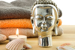 Buddha figure with candle, shells and towels Stock Photo