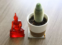 Buddha figure in meditation and cactus on wood table Stock Photos